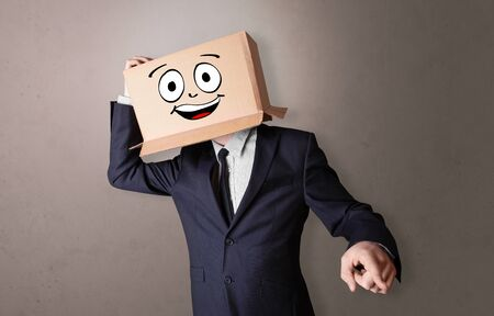 Young boy standing and gesturing with a cardboard box on his head Stok Fotoğraf