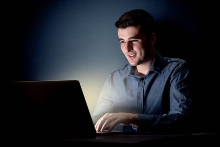 Young handsome businessman working late at night in the office with a dark background Stok Fotoğraf
