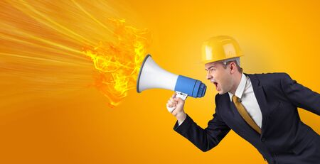 Young architect constructor yelling with megaphone with copyspace Фото со стока
