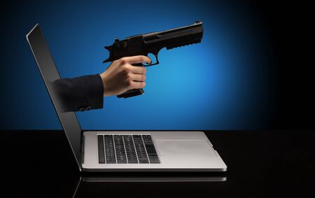 Hand with gun coming out of a laptop with sparkling effects Stok Fotoğraf