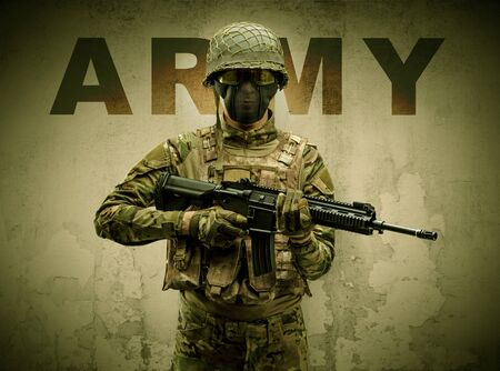 Uniformed armed soldier with damaged wall background Stok Fotoğraf