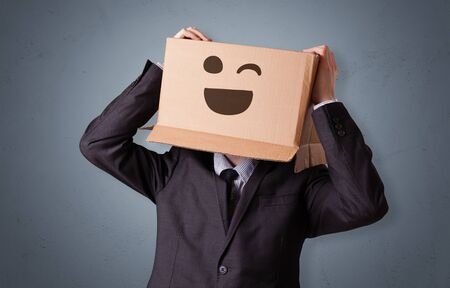 Funny man wearing cardboard box on his head with smiley face 스톡 콘텐츠