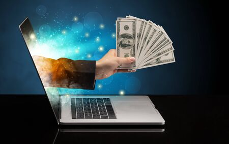 Hand with money coming out of a laptop with sparkling effects Imagens