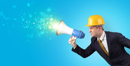 Young architect constructor yelling with megaphone and sparkling sounds