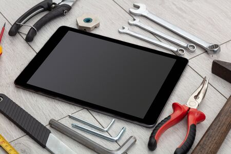 Tablet with empty screen and construction tools around Banco de Imagens - 132189802