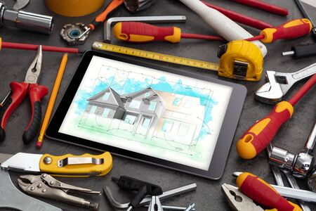 Tablet with construction tools and house plan concept Banco de Imagens