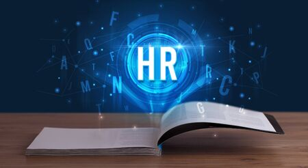 HR inscription coming out from an open book, digital technology concept