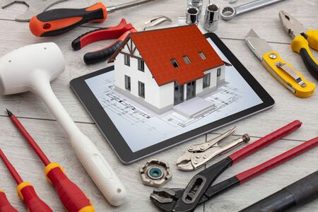 Tablet with construction tools and 3d home plan concept Banco de Imagens