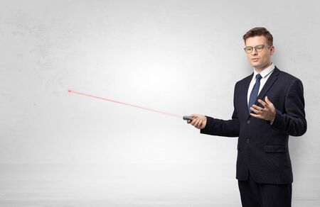 Young businessman with laser pointer and copyspace white wall