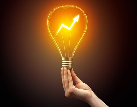 Hand holding light bulb on dark background. New Eco idea concept 免版税图像