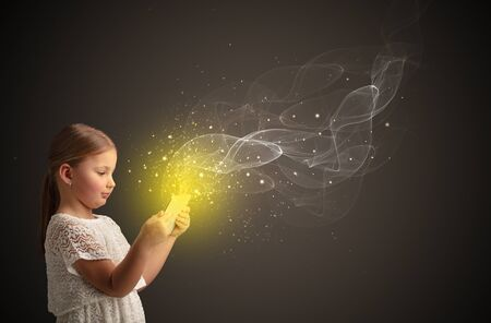 Little cute girl playing on sparkling tablet Stok Fotoğraf