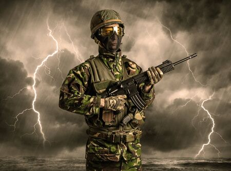 Armed soldier standing in rainy obscure weather