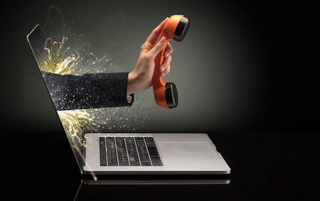 Main avec téléphone sortant d'un ordinateur portable avec des effets étincelants