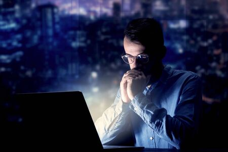 Young handsome businessman working late at night in the office with blue lights in the background Stok Fotoğraf