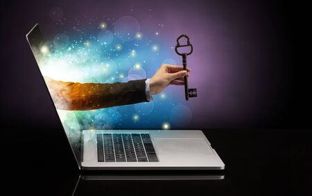 Hand with huge vintage key coming out of a laptop with sparkling effects Stok Fotoğraf