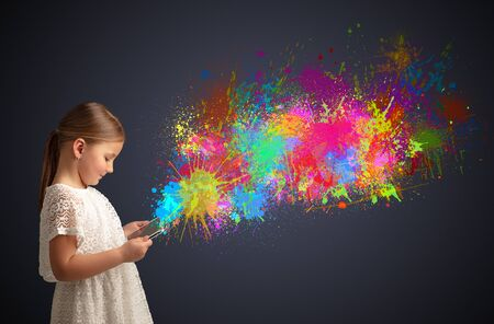 Cute little girl using tablet with colourful splash concept