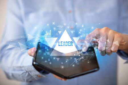 Businessman holding a foldable smartphone with LEADER inscription, business concept Banco de Imagens