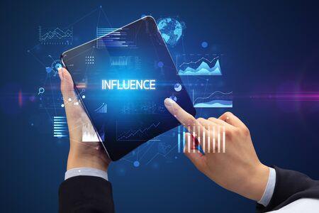 Businessman holding a foldable smartphone with INFLUENCE inscription, successful business concept Banco de Imagens