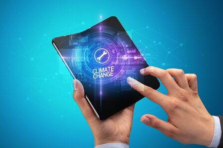 Businessman holding a foldable smartphone with WEB TRAFFIC inscription, new technology concept CLIMATE CHANGE Banco de Imagens