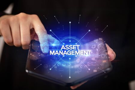 Businessman holding a foldable smartphone with ASSET MANAGEMENT inscription, new business concept