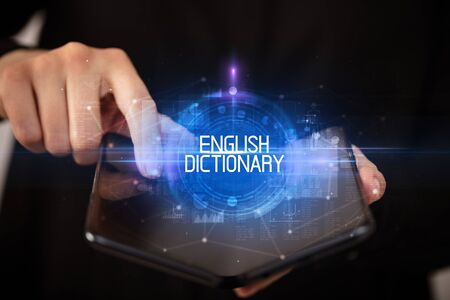 Young man holding a foldable smartphone with ENGLISH DICTIONARY inscription, educational concept