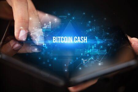 Businessman holding a foldable smartphone with BITCOIN CASH inscription, business concept Banco de Imagens
