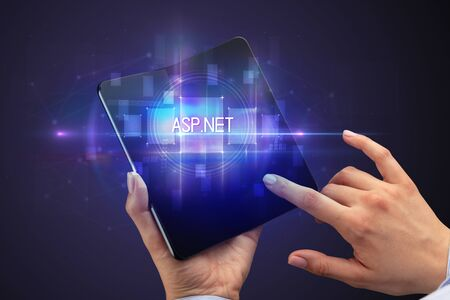 Businessman holding a foldable smartphone with ASP.NET inscription, new technology concept
