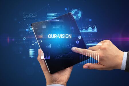 Businessman holding a foldable smartphone with OUR VISION inscription, successful business concept