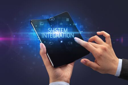 Businessman holding a foldable smartphone with SYSTEM INTEGRATION inscription, cyber security concept Banco de Imagens