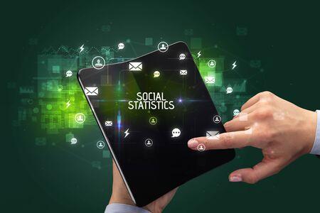 Businessman holding a foldable smartphone with SOCIAL STATISTICS inscription, social networking concept Banco de Imagens