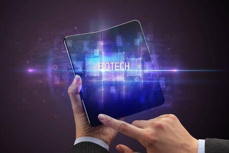 Businessman holding a foldable smartphone with BIOTECH inscription, new technology concept Banco de Imagens