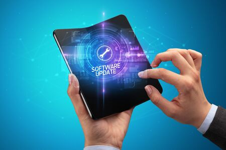 Businessman holding a foldable smartphone with DEVELOPMENT inscription, new technology concept SOFTWARE UPDATE