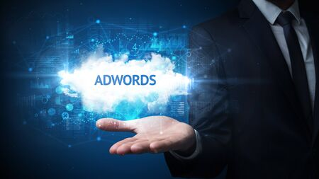Hand of Businessman holding ADWORDS inscription, successful business concept Imagens