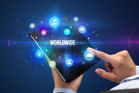 Businessman holding a foldable smartphone with WORLDWIDE inscription, social media concept Banco de Imagens