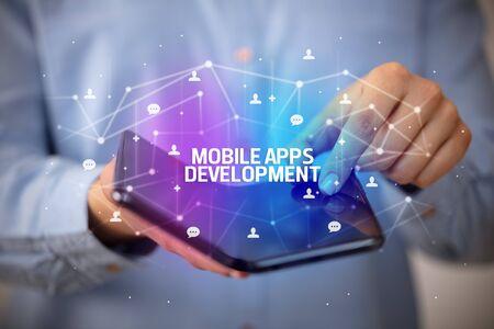 Businessman holding a foldable smartphone with MOBILE APPS DEVELOPMENT inscription, new technology concept Banco de Imagens