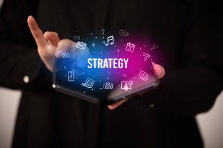 Businessman holding a foldable smartphone with STRATEGY inscription, social media concept Banco de Imagens