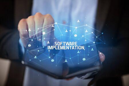 Businessman holding a foldable smartphone with SOFTWARE IMPLEMENTATION inscription, new technology concept Banco de Imagens