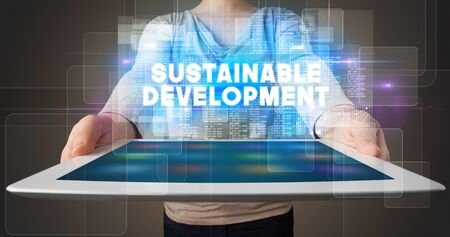 Young business person working on tablet and shows the inscription: SUSTAINABLE DEVELOPMENT 写真素材