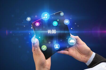 Businessman holding a foldable smartphone with VLOG inscription, social media concept