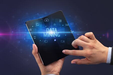 Businessman holding a foldable smartphone with DATA MINING inscription, cyber security concept