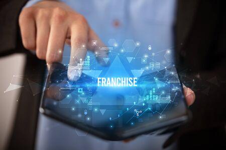 Businessman holding a foldable smartphone with FRANCHISE inscription, business concept Banco de Imagens