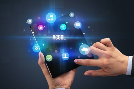 Businessman holding a foldable smartphone with #COOL inscription, social media concept