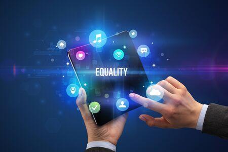 Businessman holding a foldable smartphone with EQUALITY inscription, social media concept Banco de Imagens