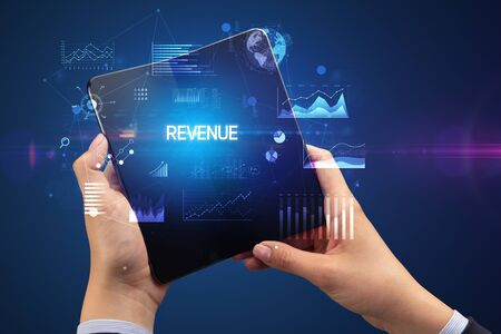 Businessman holding a foldable smartphone with REVENUE inscription, successful business concept