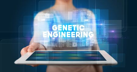 Young business person working on tablet and shows the inscription: GENETIC ENGINEERING 写真素材