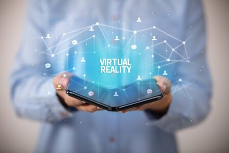 Businessman holding a foldable smartphone with VIRTUAL REALITY inscription, new technology concept