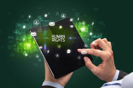 Businessman holding a foldable smartphone with HUMAN RIGHTS inscription, social networking concept
