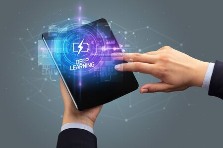 Businessman holding a foldable smartphone with WEB DESIGN inscription, new technology concept DEEP LEARNING