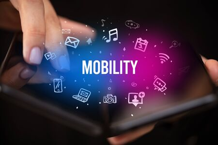 Businessman holding a foldable smartphone with MOBILITY inscription, social media concept Banco de Imagens