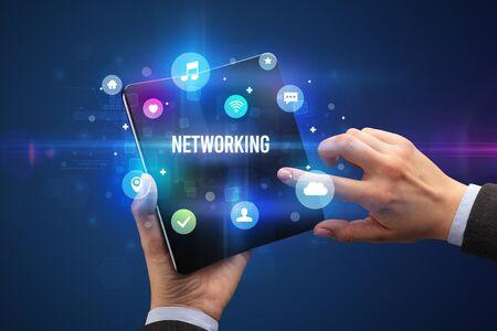 Businessman holding a foldable smartphone with NETWORKING inscription, social media concept Banco de Imagens